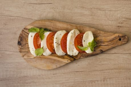 slices-mozzarella-cheese-tomatoes-with-herb-chopping-board-against-wooden-backdrop